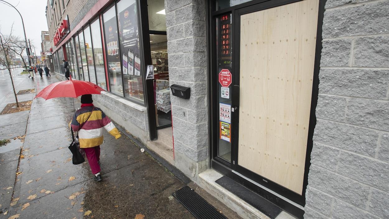 Une porte d'un établissement dont la vitre a été remplacée par une planche de bois.