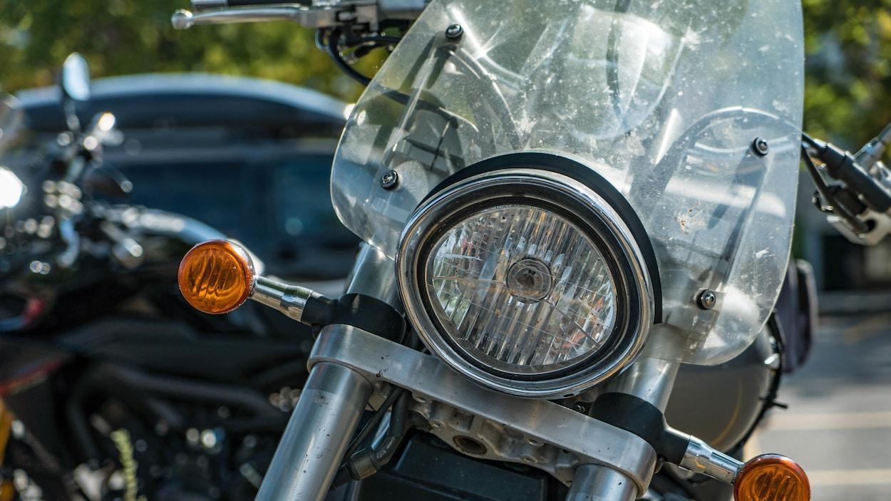 Une motocyclette noire et argentée qui est stationnée.