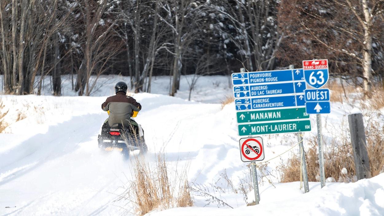 Un motoneigiste circule sur un sentier.