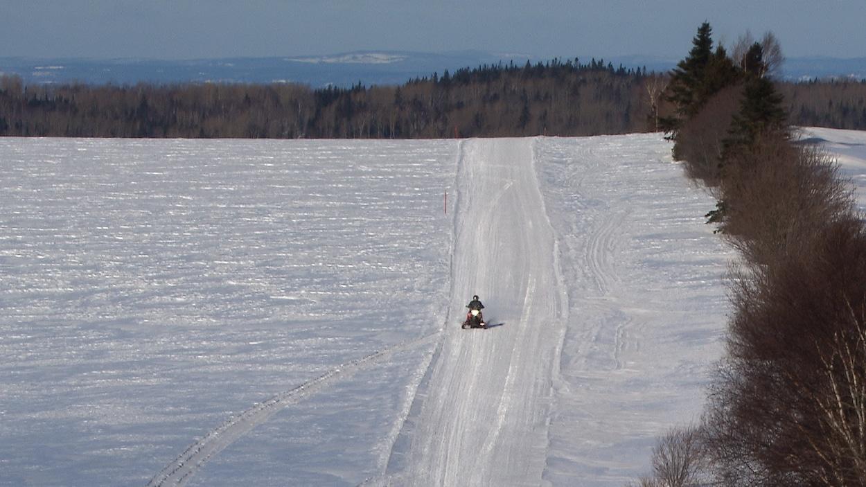 Un motoneigiste se promène sur un sentier près de Trois-Pistoles.