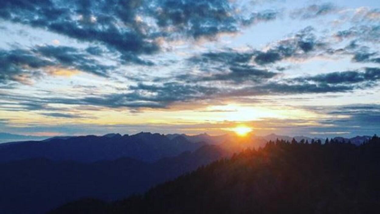 Une vue du soleil couchant dans les montagnes.