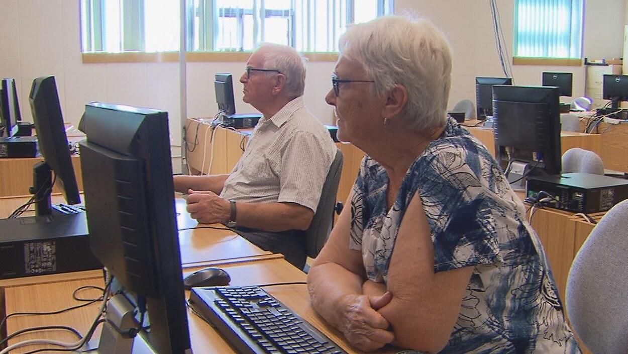 Deux aînés assis devant des ordinateurs écoutent les explications du formateur.