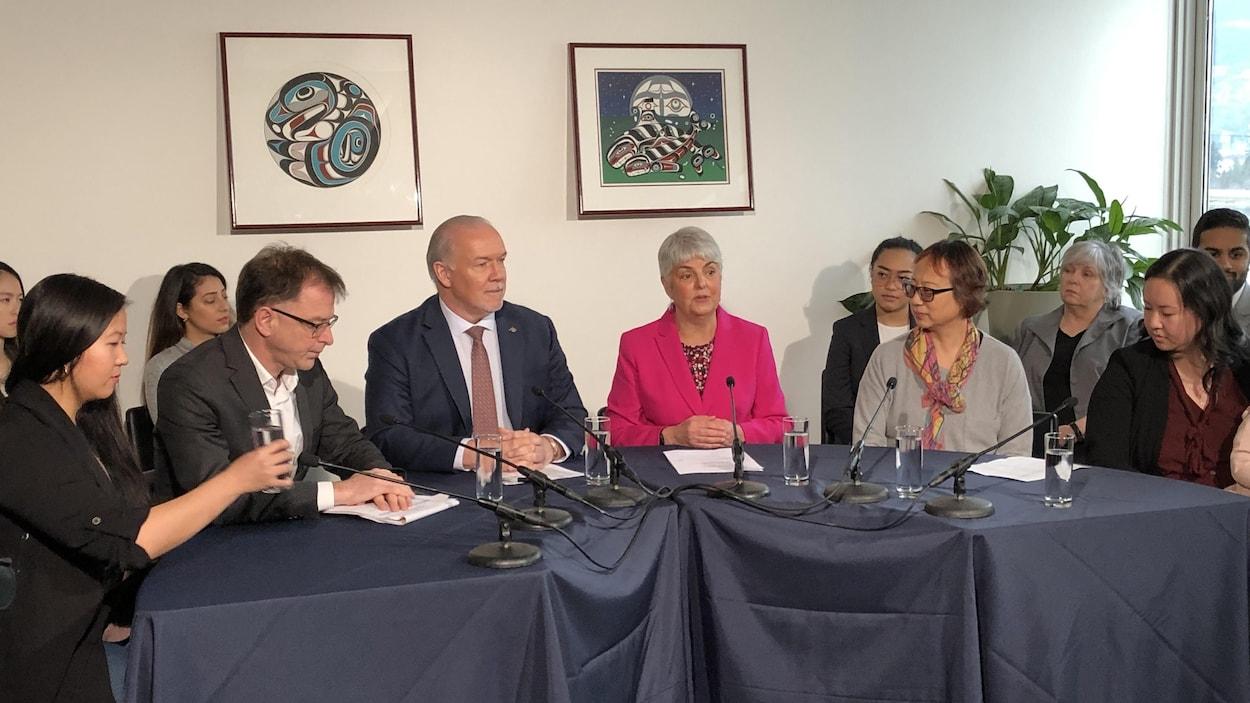 Plusieurs intervenants, dont John Horgan, Carol James et Adrian Dix sont assis derrière une table.