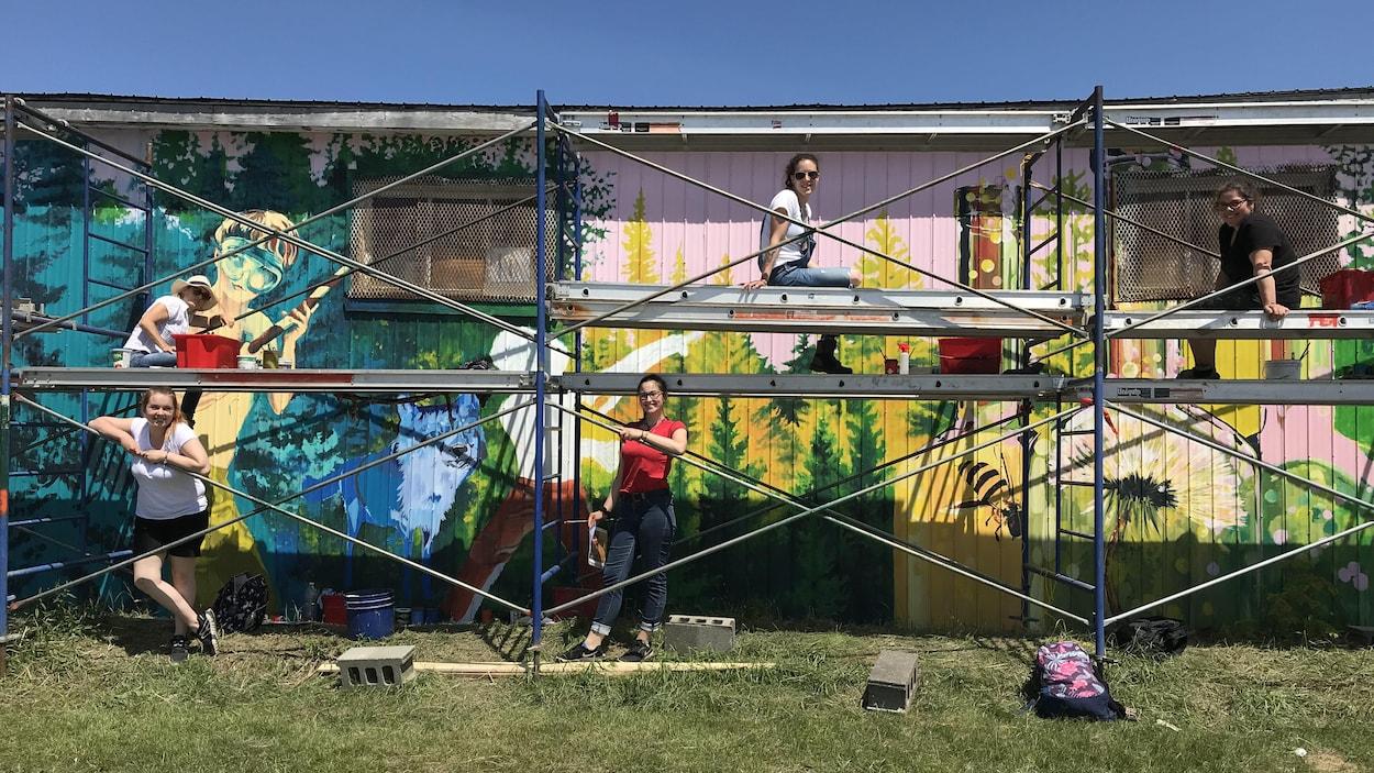 Cinq femmes sont assises dans des échafaudages devant un bâtiment où elles peignent une murale.