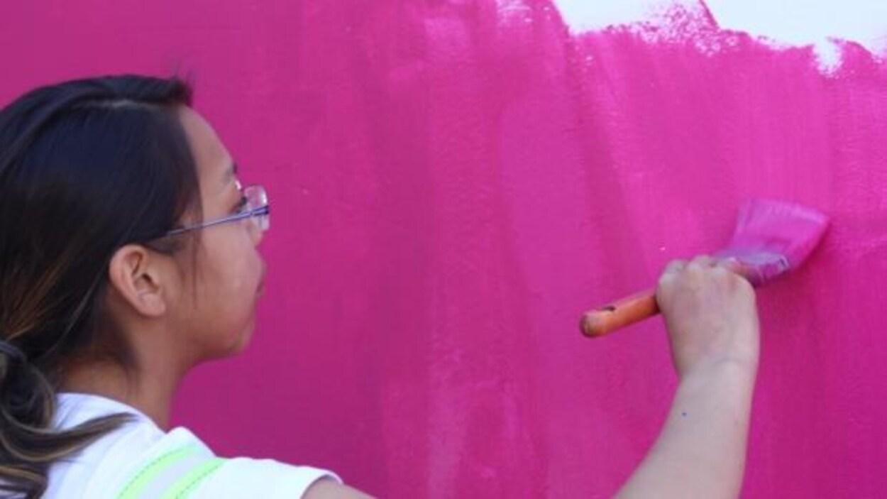 Une jeune artiste en train de peindre.