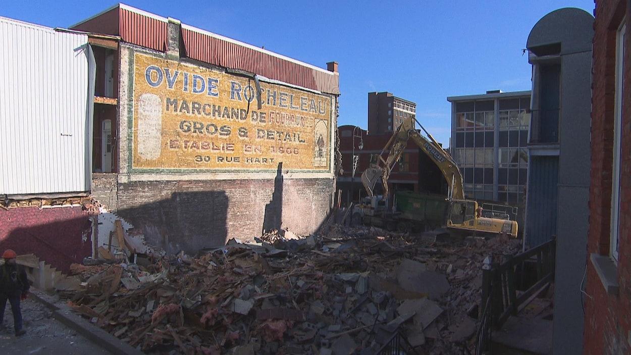 Une pelle mécanique et des débris devant une murale centenaire.