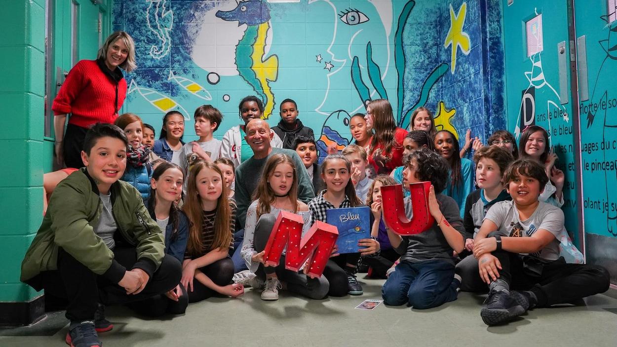 Photo en couleur d'un groupe d'enfants de 5e année du primaire devant une murale peinte sur un mur de leur école. En arrière plan, on voit sur la murale un hippocampe licorne et un croissant de lune.