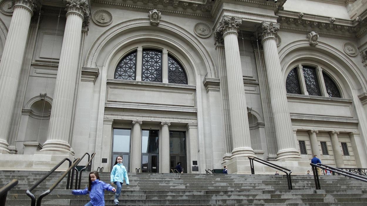 Des enfants descendent les marches menant à l'entrée du Metropolitan Museum of Art de New York.