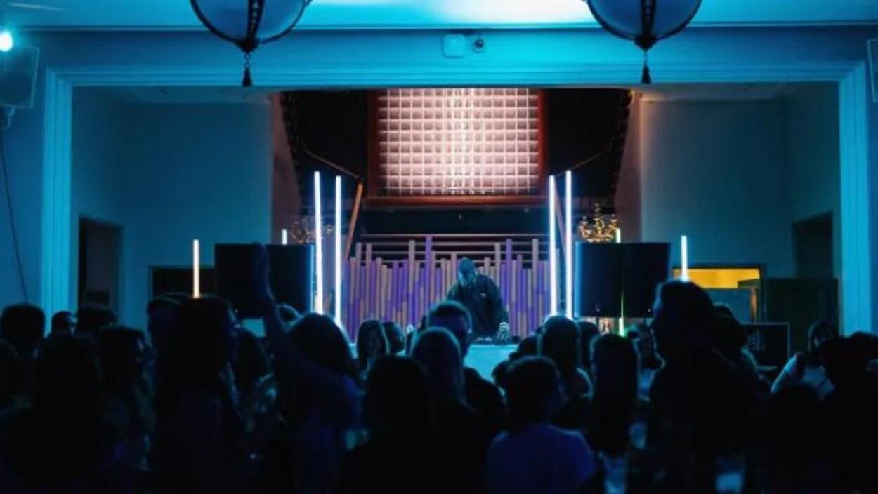 Une soirée de Chiaroscuro au musée des beaux-arts de Montréal, on voit un DJ mixer et des jeunes danser devant.