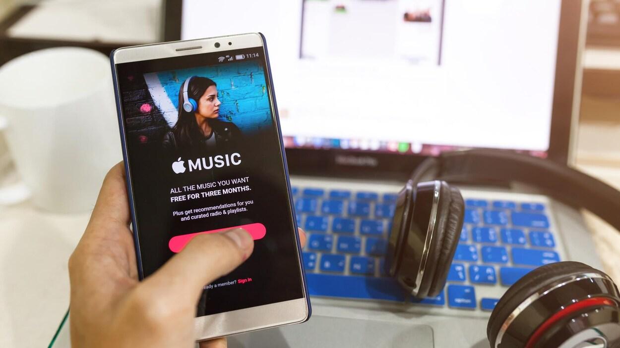 une personne tient un téléphone dans sa main, on voit aussi un ordinateur et un casque d'écoute.