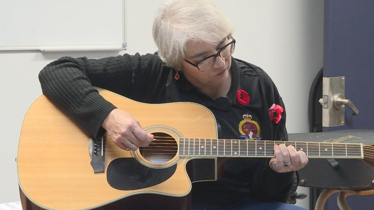 Nathalie Vanasse joue de la guitare.