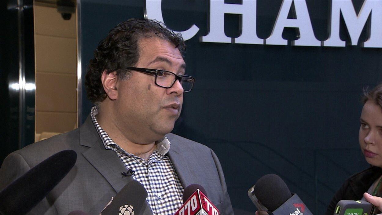 Naheed Nenshi répond aux journalistes devant la porte du conseil municipal.