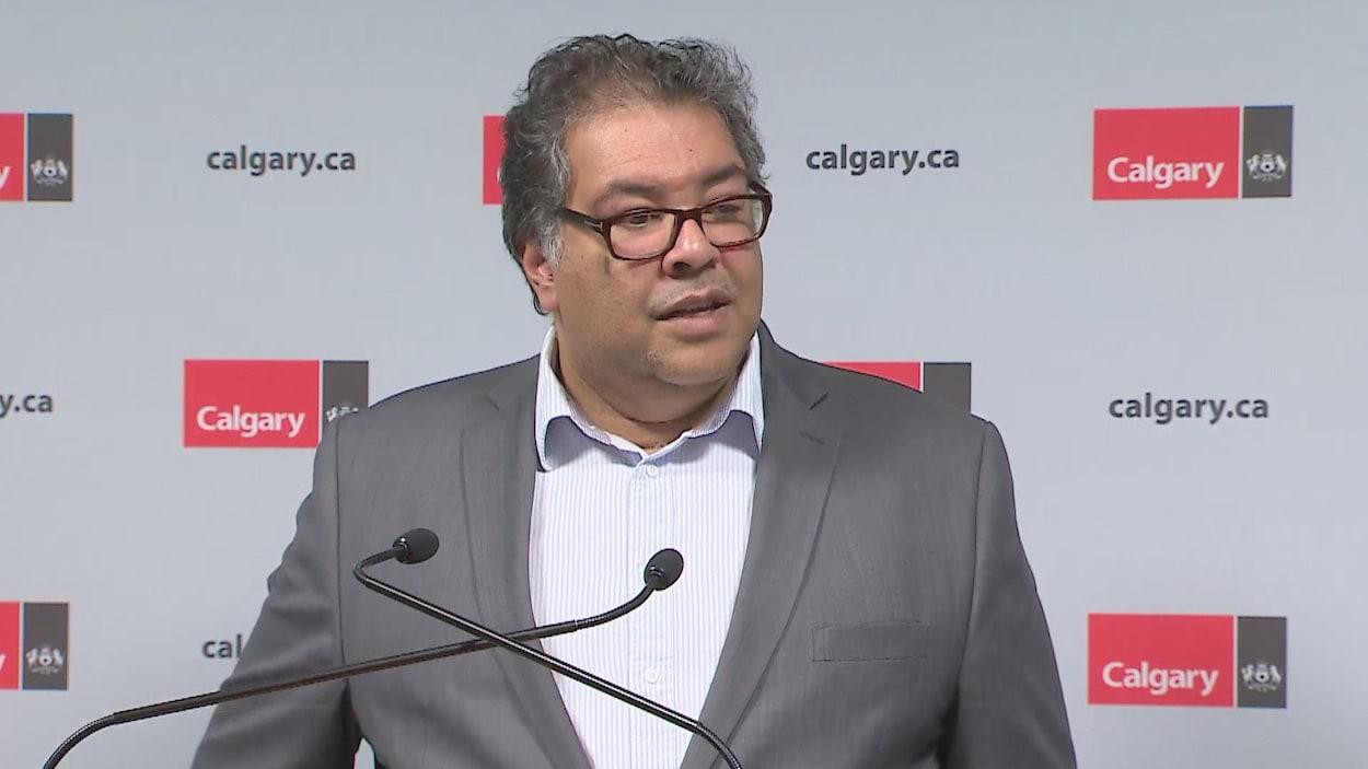 un homme avec des lunettes, parle au micro, derrière un pupitre.
