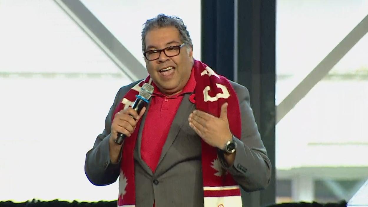 Naheed Nenshi, avec un foulard de l'équipe olympique canadienne au coup, s'adresse aux centaines de personnes présentes dans la salle.