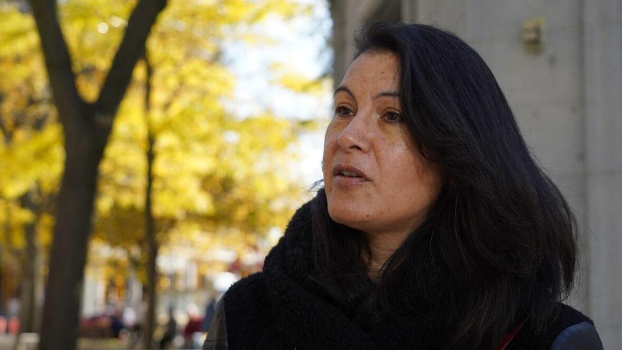 La femme au longs cheveux noirs en plan rapproché avec des arbres derrière elle.