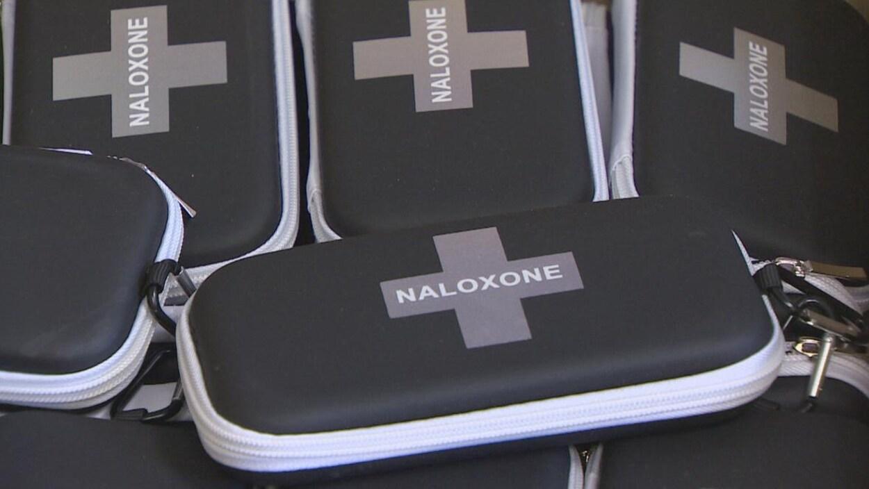 Photo de trousses noires marquées d'une croix avec la mention naloxone.