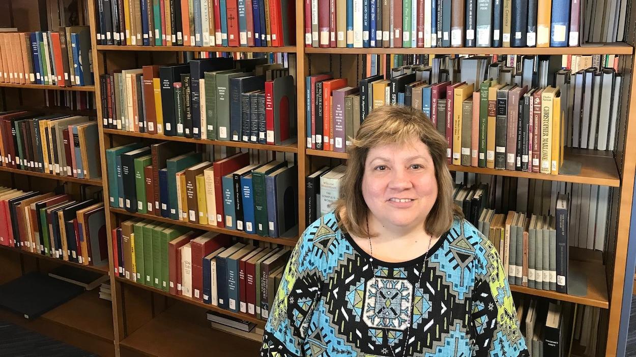 Nancy Daniel pose devant les rayons de sa bibliothèque.