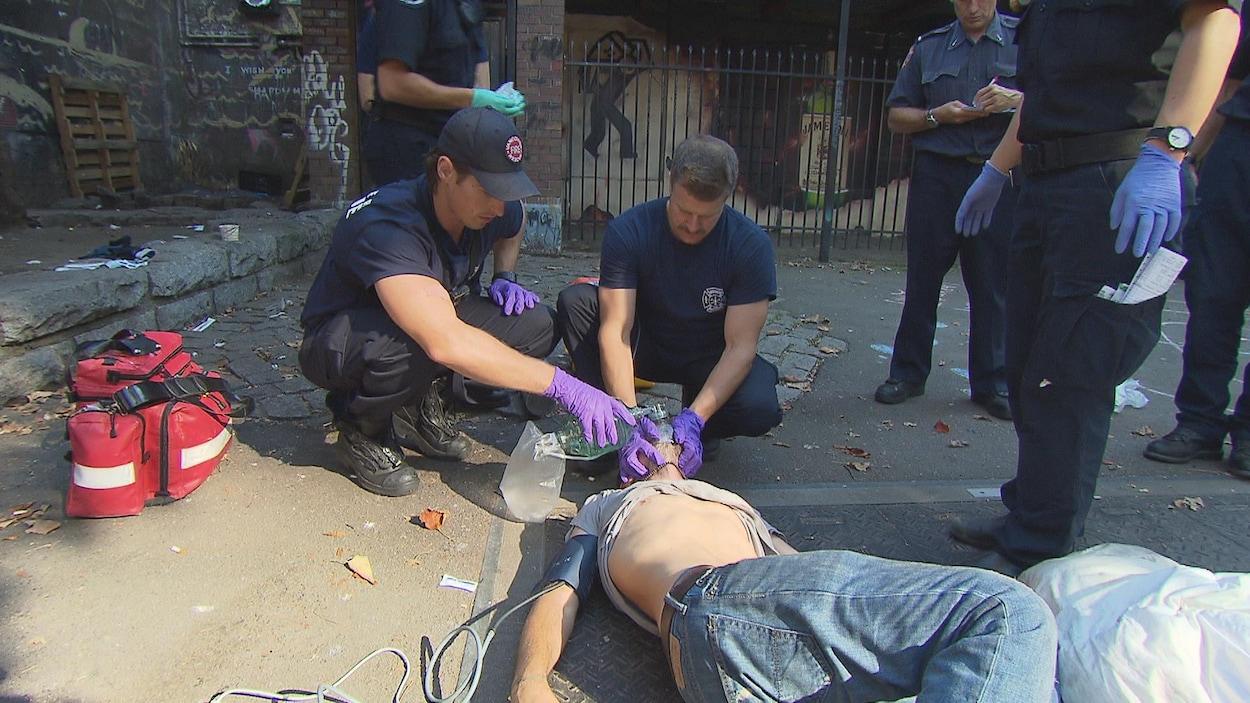 Deux pompiers tentent de réanimer une personne avec un masque à oxygène.