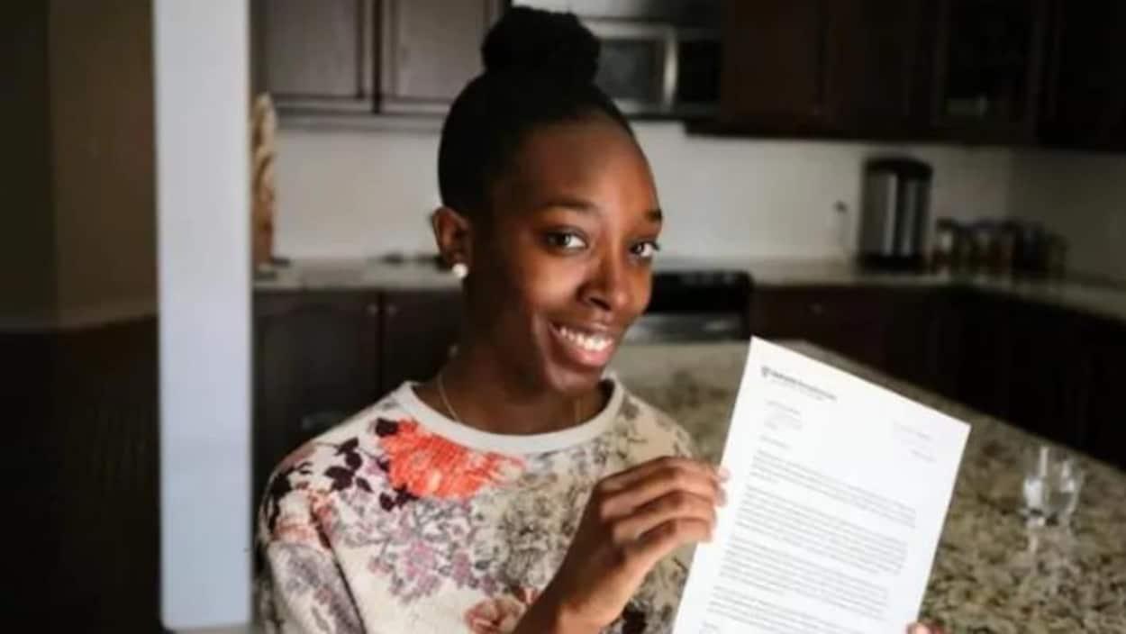 Na'Shantéa Miller avec sa lettre d'admission à Harvard - elle a les cheveux noirs tirés en chignon, elle porte un chandail blanc avec des fleurs, elle a la peau noir, les yeux noirs et elle sourit