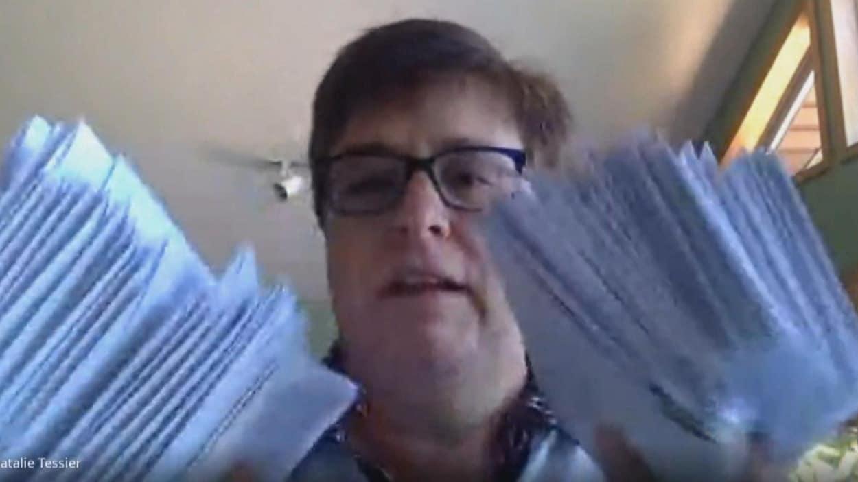 Natalie Tessier tient au moins une vingtaine d'enveloppes dans chaque main.