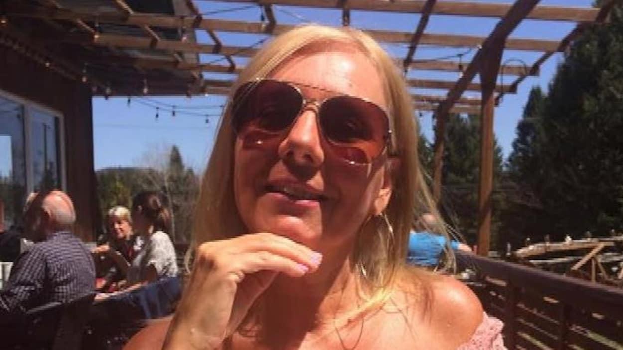 Une femme souriante en vacances, assise à une table.