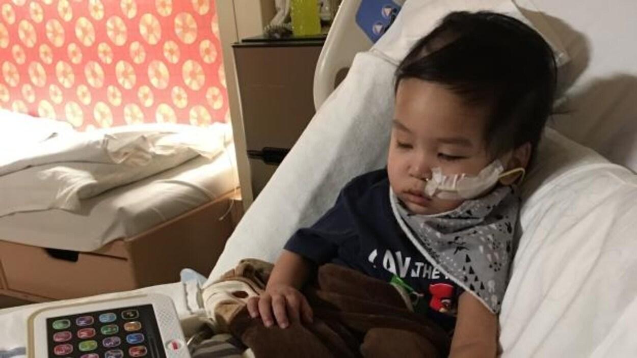 Un bambin allongé sur un lit avec une sonde dans le nez.