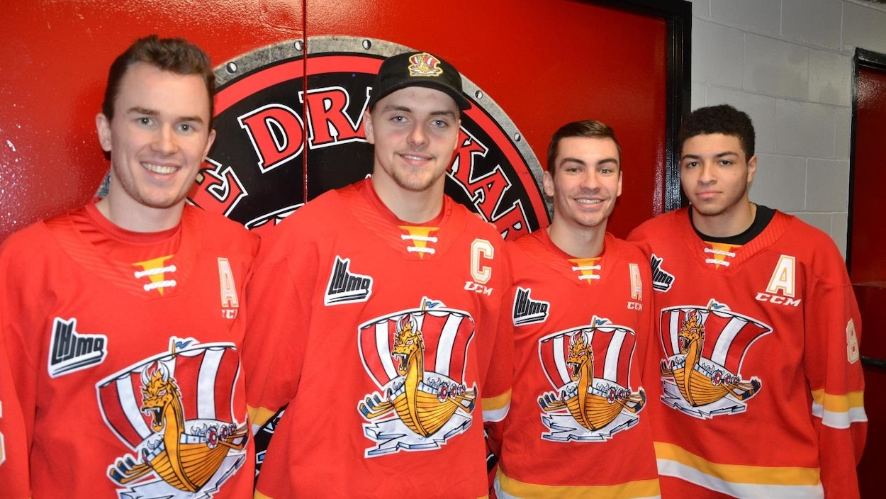 Quatre hockeyeurs du Drakkar sourient à la caméra.