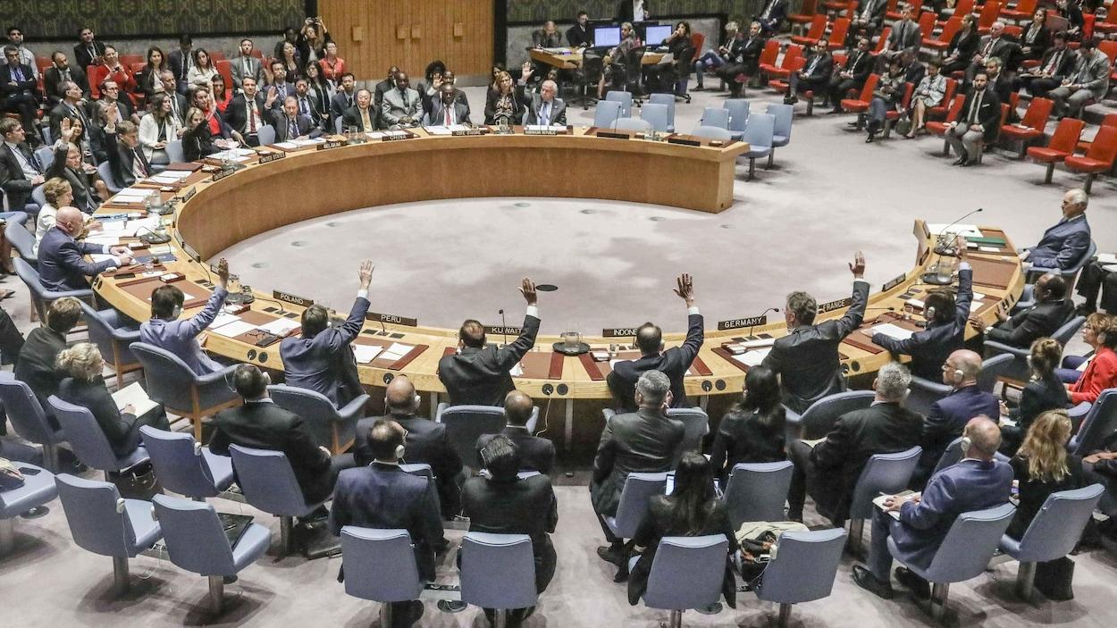 La table en forme de fer à cheval du conseil de sécurité avec ses membres assis autour d'elle en train de voter sur une motion.