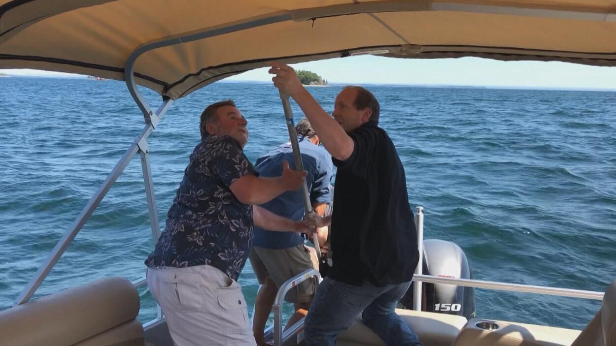 Trois hommes à l'arrière du bateau aident le naufragé à monter à bord.