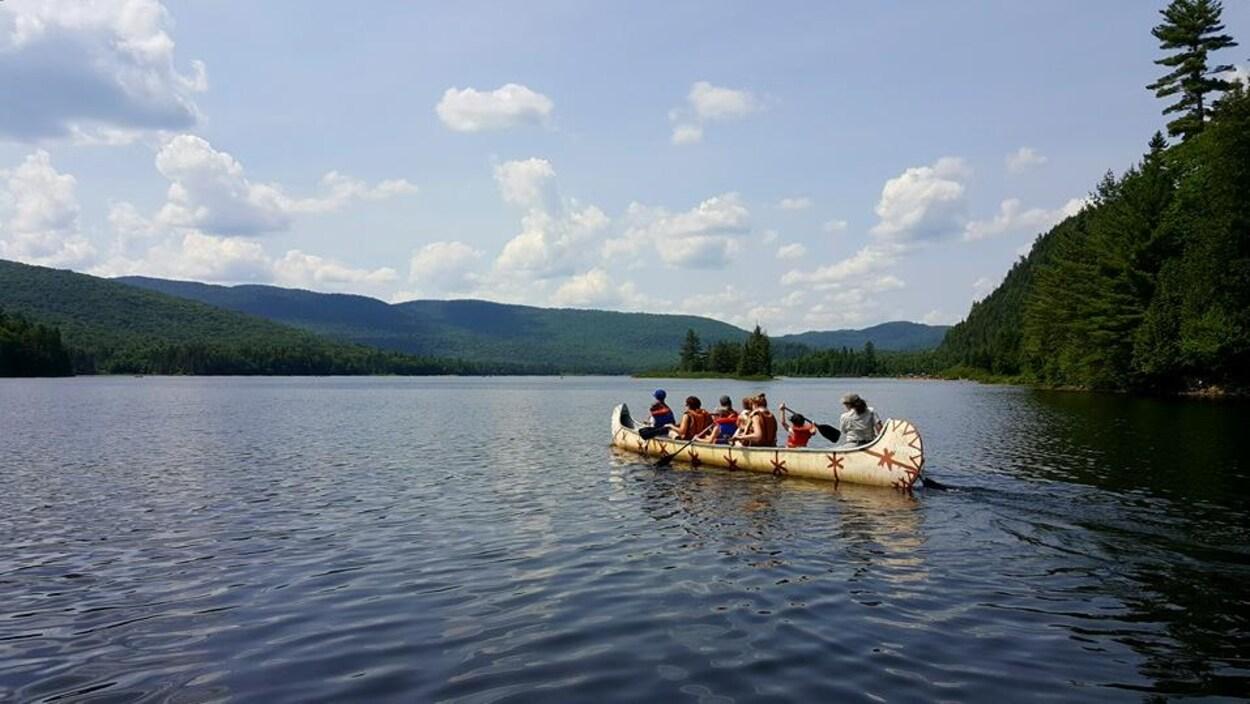 Des utilisateurs de Navette Nature en rabaska sur un lac.