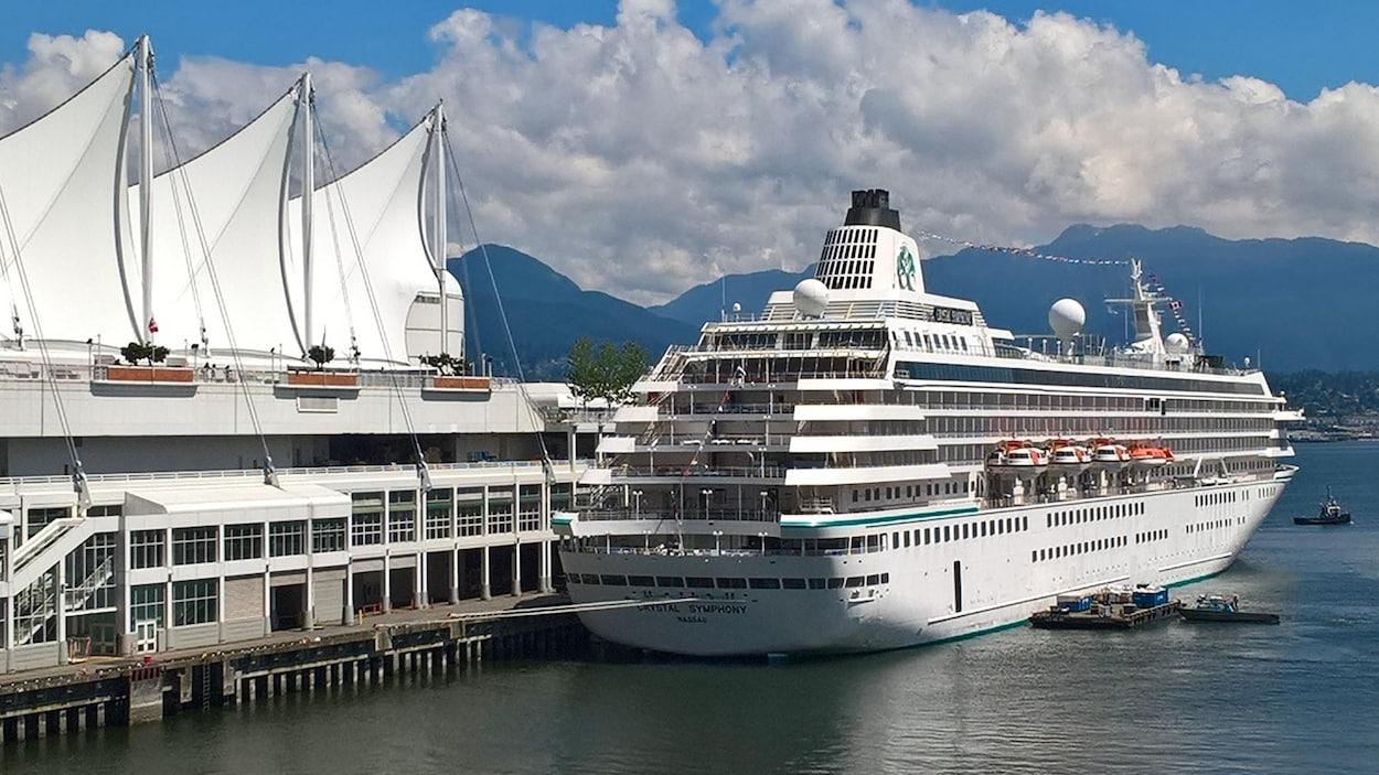 Un navire de croisière est amarré dans le port de Vancouver à côté de trois voiles de la Place du Canada avec des montagnes en arrière-plan.