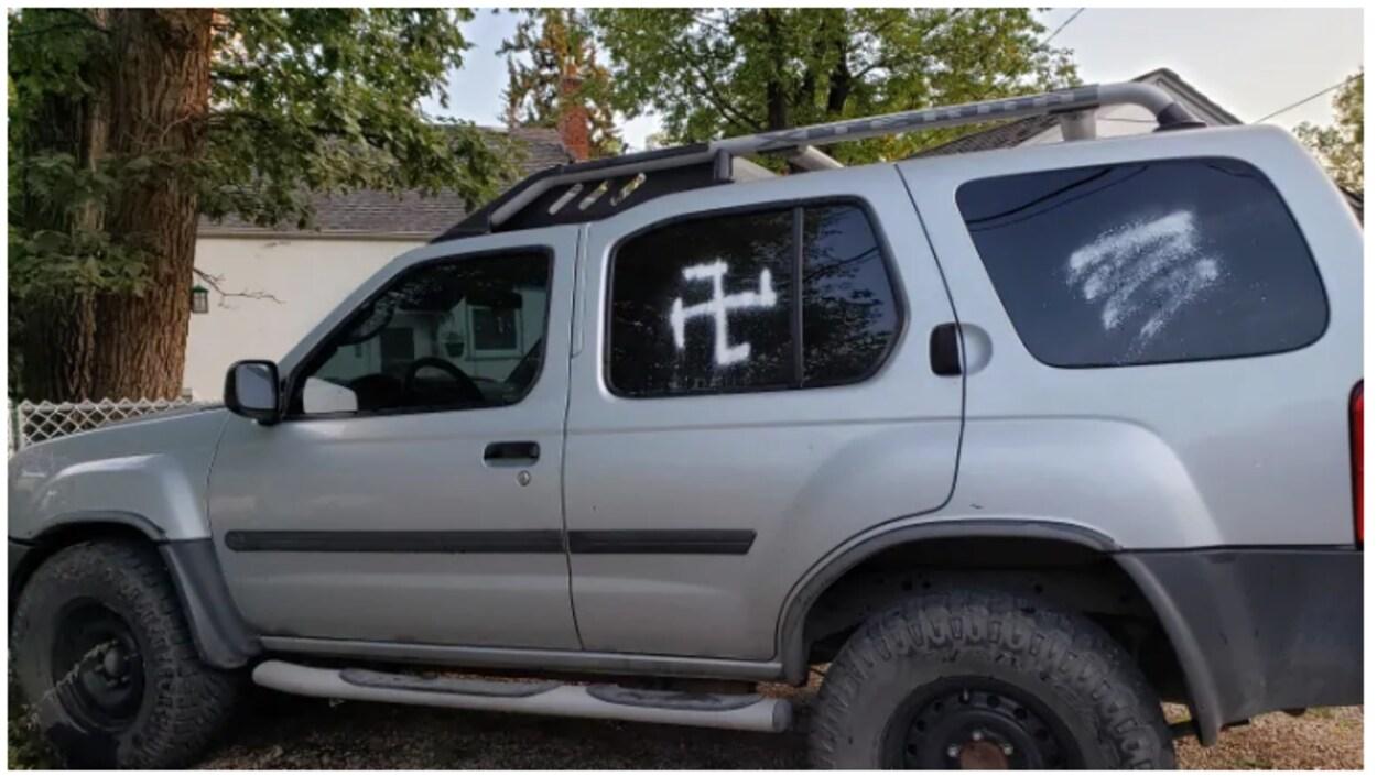 Une voiture avec une croix gammée sur la vitre centrale.
