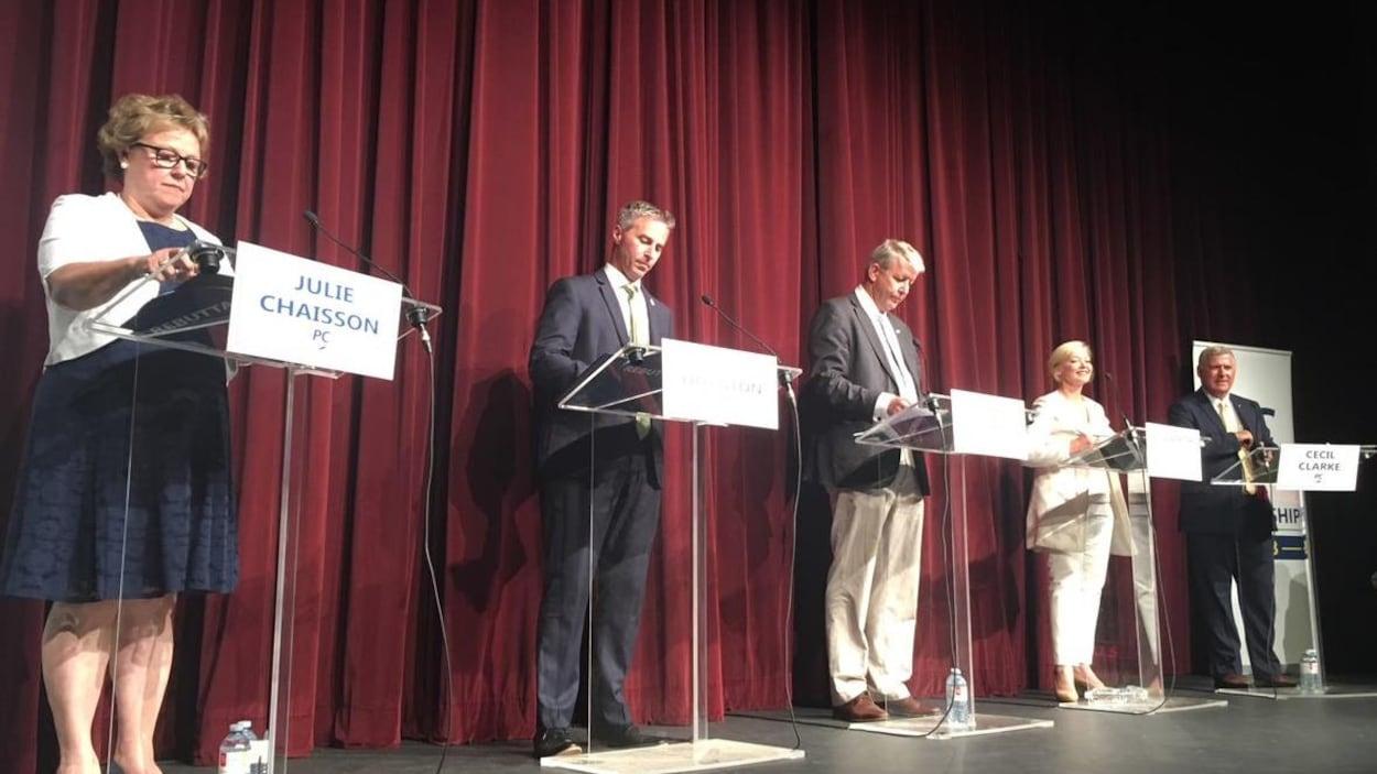 Les cinq candidats à la direction sont chacun à leur podium sur une scène, lors d'un forum, à Tusket.