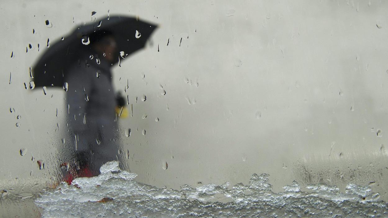 Mélange de neige et de pluie observé à travers le pare-brise d'une automobile.