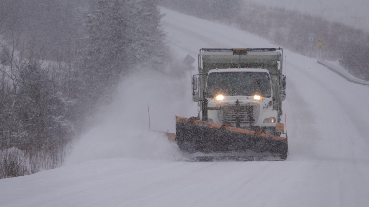 Une déneigeuse pendant une tempête de neige