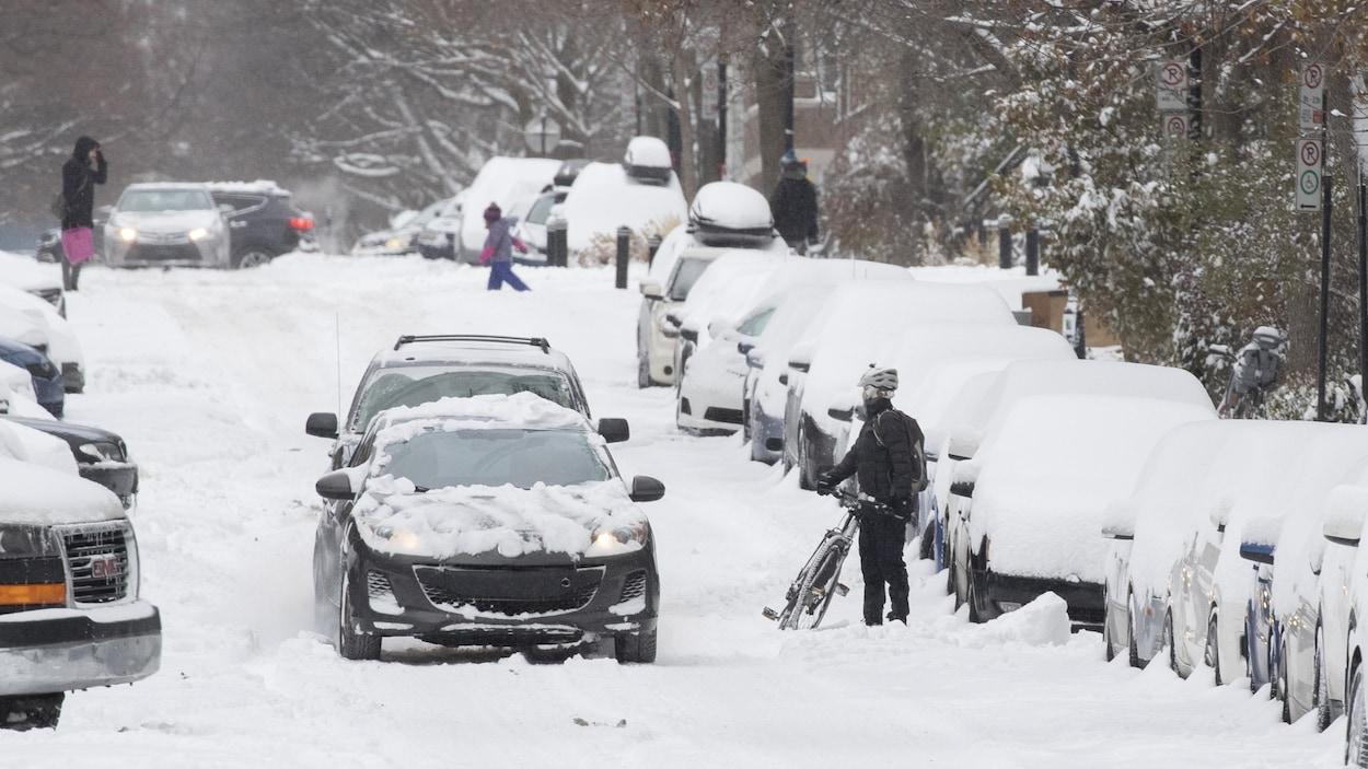 Une rue de Montréal et des voitures ensevelies sous la neige.