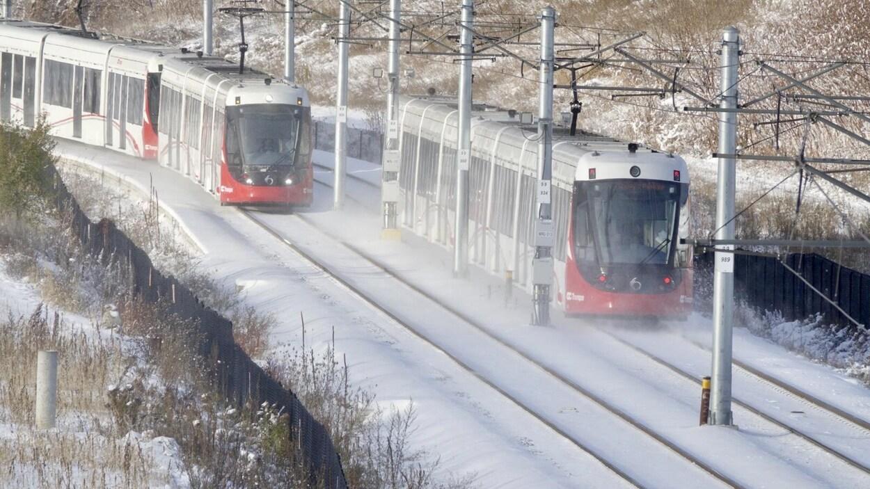 Deux trains se déplacent sur les rails enneigés.