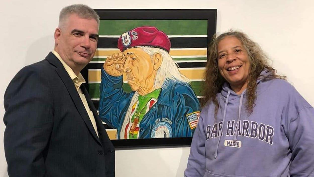 Nelson White pose avec une femme devant son tableau Elder Veteran.