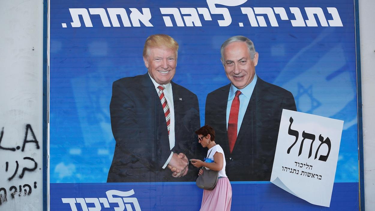 Une femme passant devant une affiche géante montrant Nétanyahou aux côtés de Trump, tout sourire.