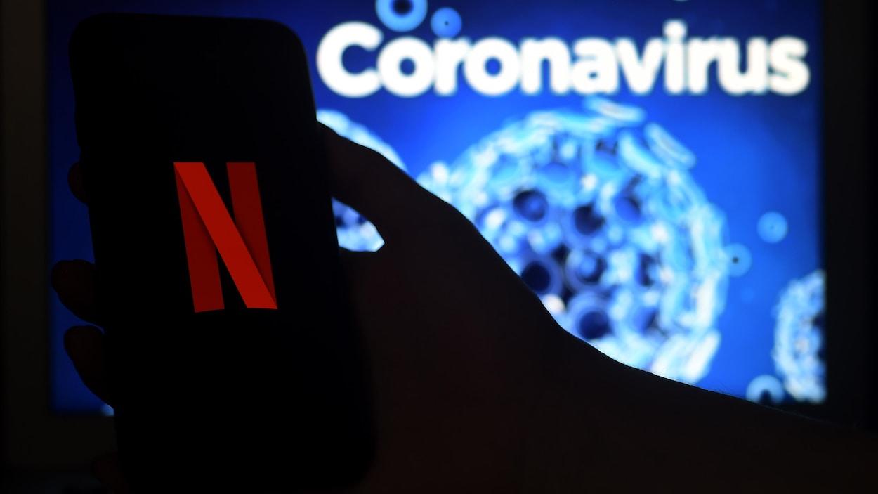 Un écran de téléphone portable affiche le logo de Netflix sur un fond graphique d'illustration du coronavirus.
