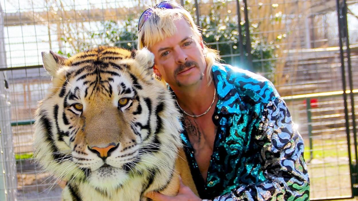 Un homme à la coupe Longueuil blonde enlace un tigre.