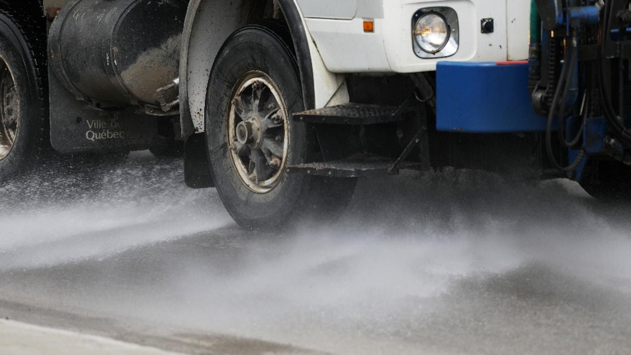 Un camion de la voirie projette un jet d'eau le long d'une rue.