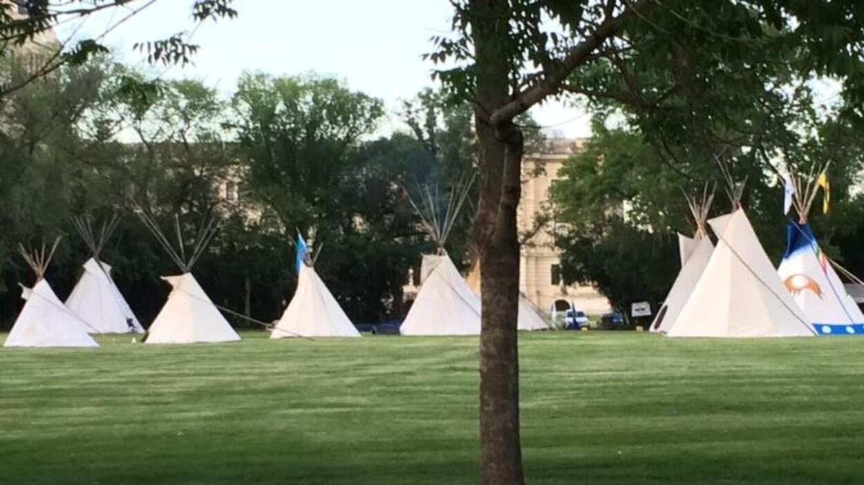 Neuf tipis sont installés sur le gazon devant l'Assemblée législative de la Saskatchewan.