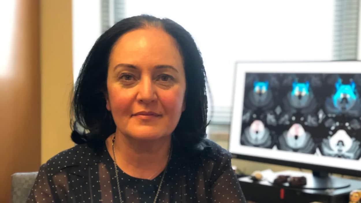 Une femme pose pour la photo avec un écran d'imagerie de cerveau en arrière-fond.