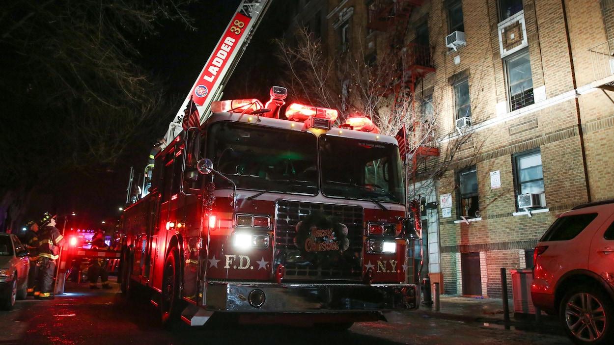 L'échelle d'un camion de pompier est déployée au-dessus de l'immeuble en flammes.