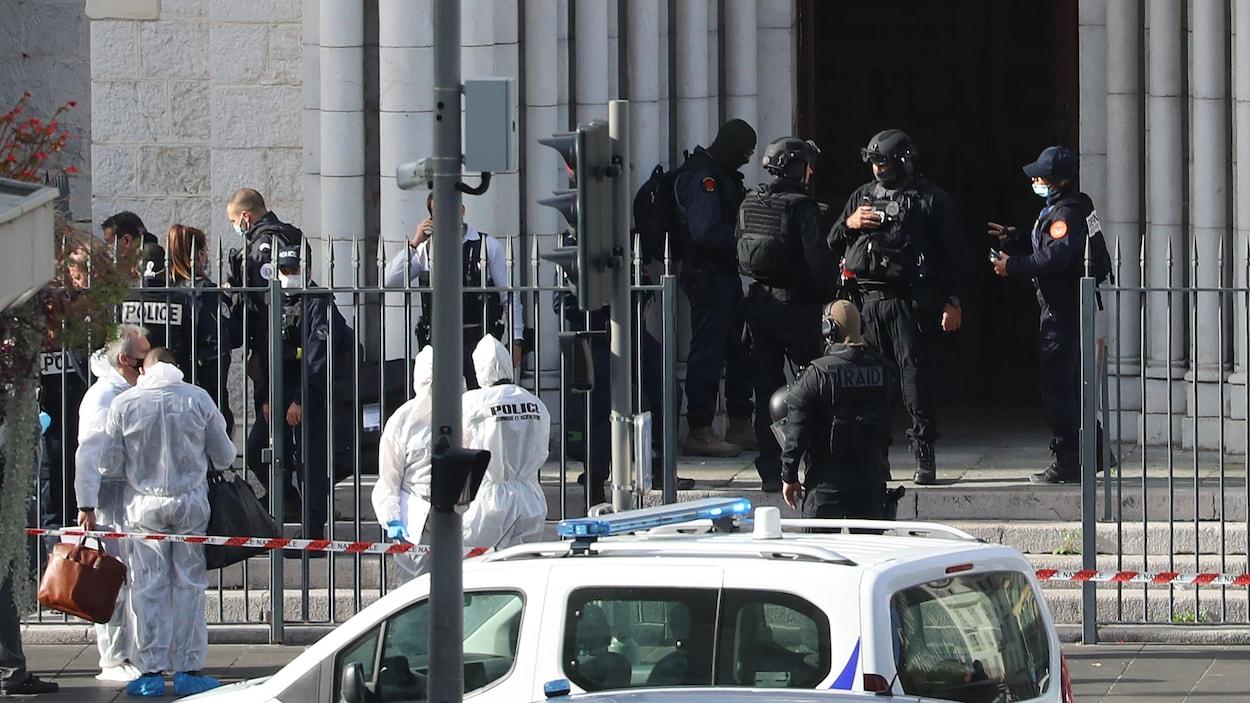 De nombreux policiers se trouvent derrière un cordon de sécurité devant la porte de l'église.