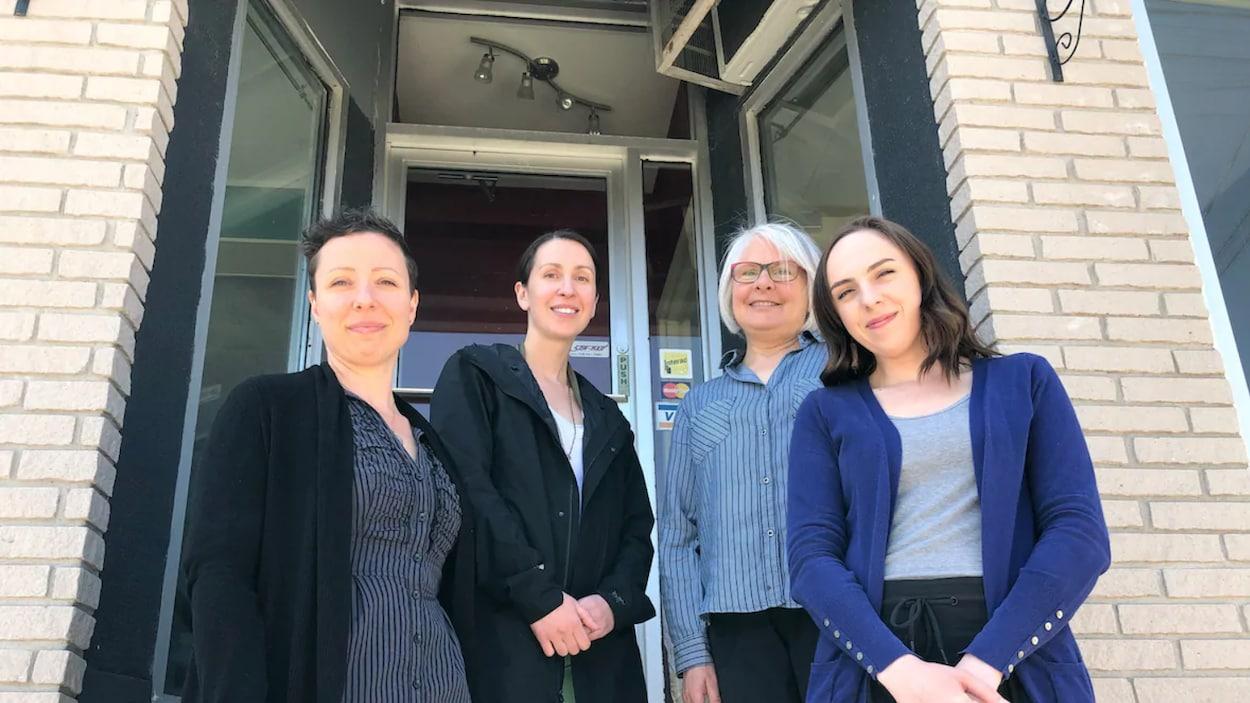Quatre femmes devant une porte.