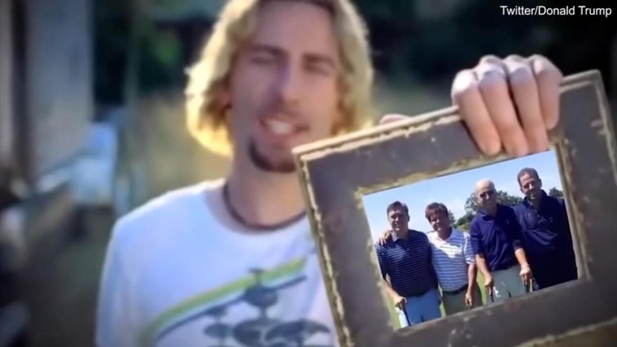 Un homme tient un cadre dans lequel apparaît une photo, ajoutée par montage, où on voit Joe Biden entouré de trois hommes.