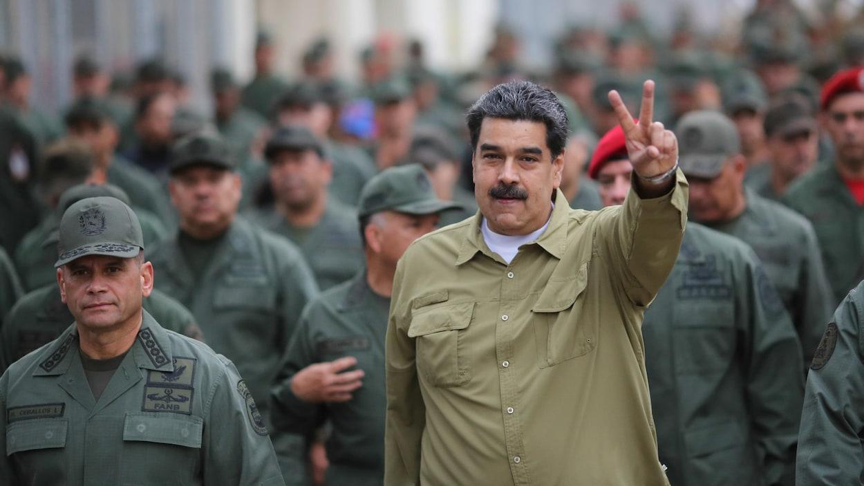 Un homme vêtu d'une chemise kaki fait un geste de victoire avec ses doigts.