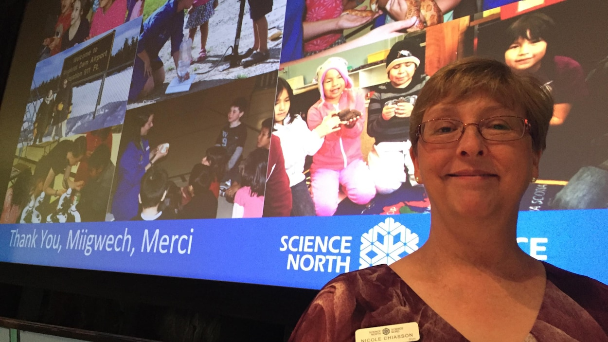 Nicole Chiasson devant quelques photos d'activités réalisées avec de jeunes autochtones.
